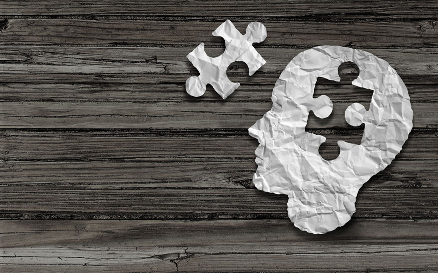 39567160 - mental health symbol puzzle and head brain concept as a human face profile made from crumpled white paper with a jigsaw piece cut out on a rustic old double page spread horizontal wood background.