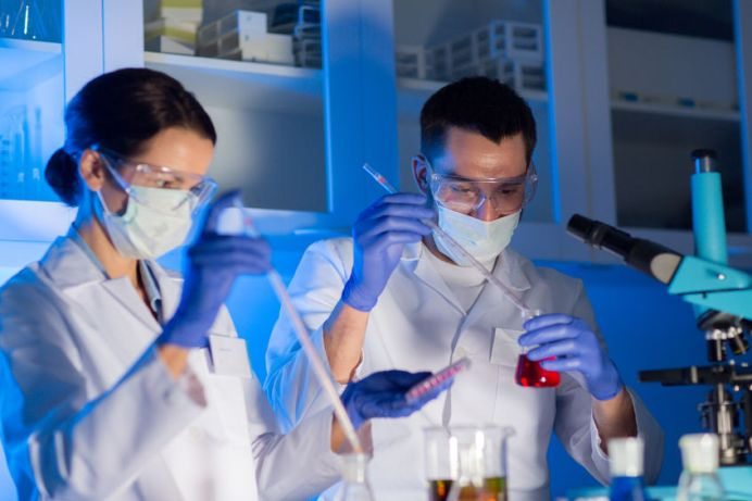 45974315 - close up of young scientists with pipette and flasks making test or research in clinical laboratory